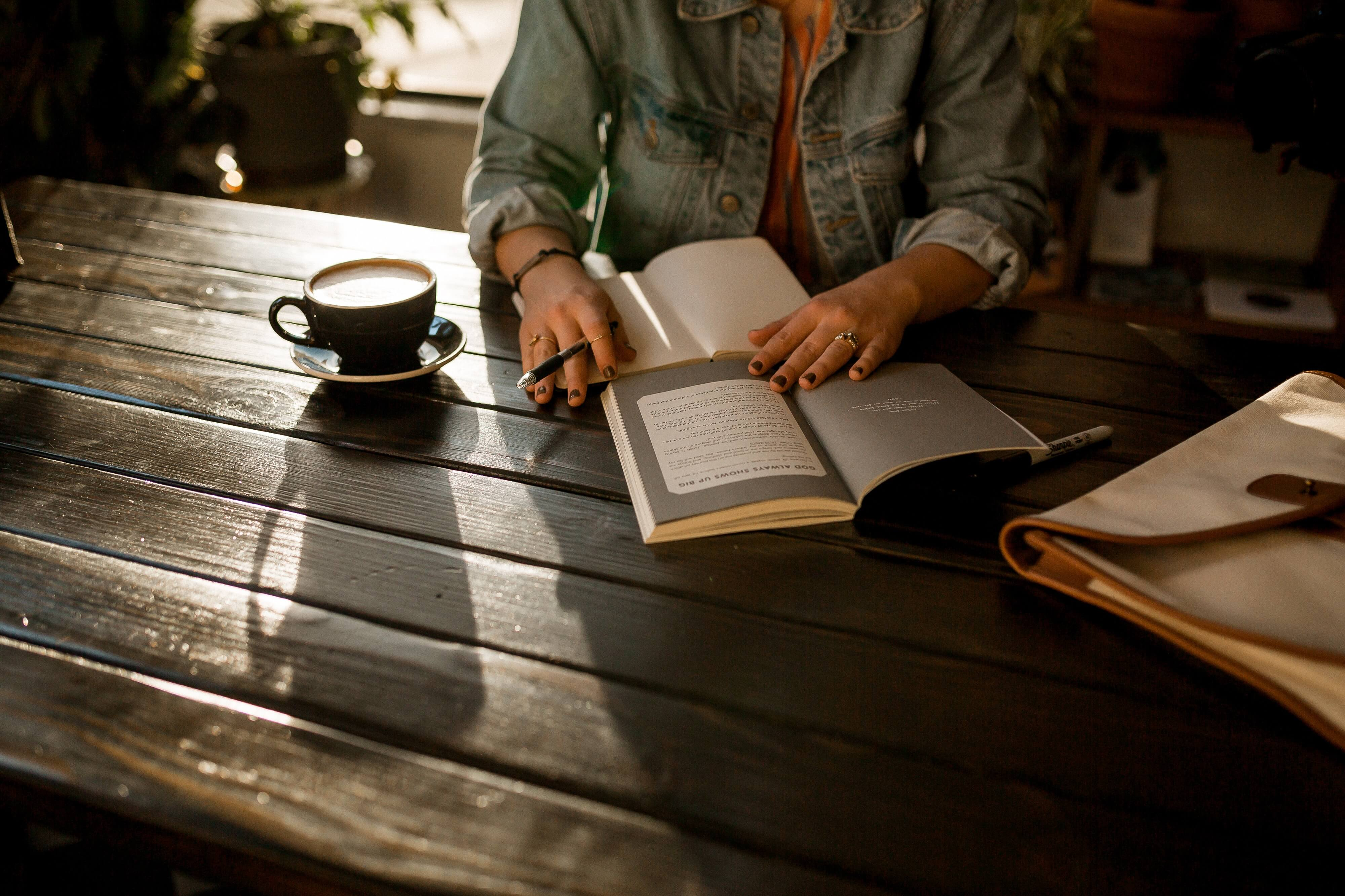 Person with a denim jacket writing on a wooden table, with a cup of coffee