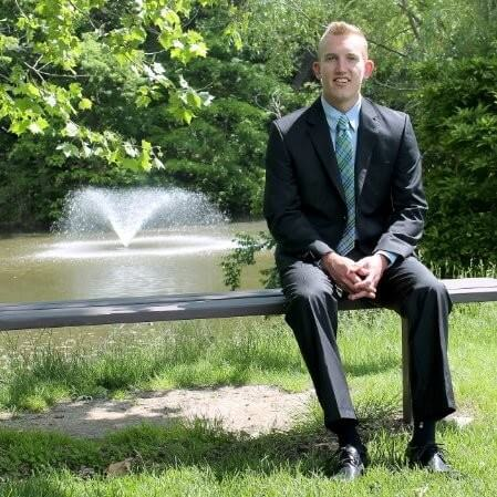 Man in a suit sitting on a bench in a green park, with a fountain in the background, looking at the camera