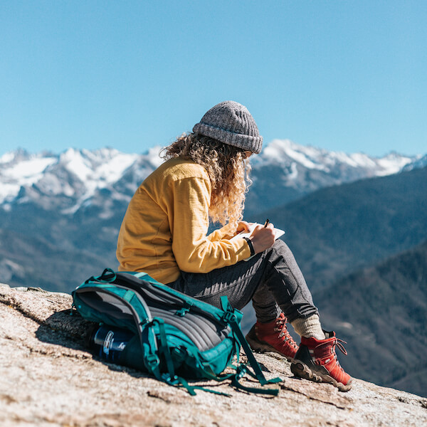 Woman Sitting on Rock writing, with mountains in the background